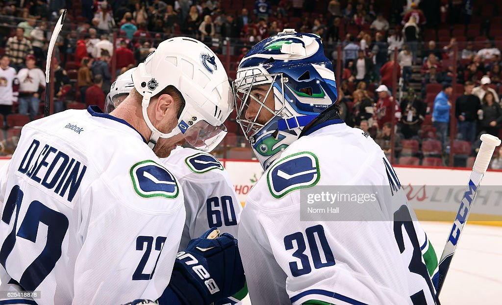 Daniel Sedin #22 and goalie Ryan Miller #30 of the Vancouver Canucks bump helmets in celebration of their 4-1 victory against the Arizona Coyotes at Gila River Arena on November 23, 2016 in Glendale, Arizona.