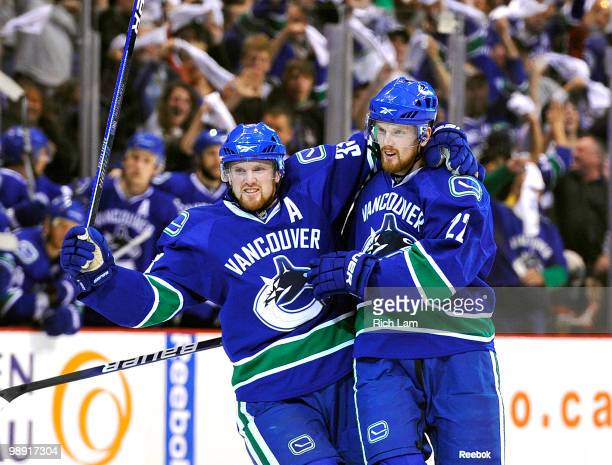 Daniel Sedin and Henrik Sedin of the Vancouver Canucks celebrate after Daniel Sedin scored against the Chicago Blackhawks during the first period in...