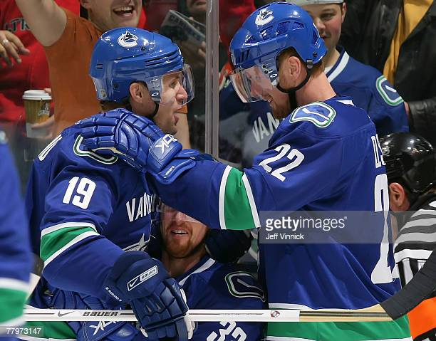 Daniel Sedin and Henrik Sedin of the Vancouver Canucks congratulate teammate Markus Naslund after scoring against the Calgary Flames during their...
