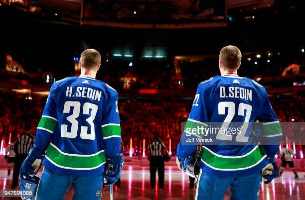 Daniel Sedin and Henrik Sedin of the Vancouver Canucks listen to the national anthems during their NHL game against the Anaheim Ducks at Rogers Arena...