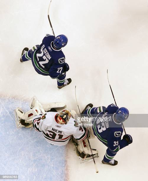 Daniel Sedin and Henrik Sedin of the Vancouver Canucks stand in front of Antti Niemi of the Chicago Blackhawks in Game Four of the Western Conference...