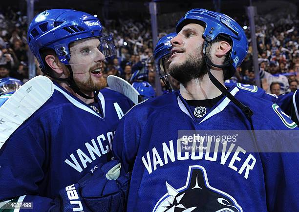 Daniel Sedin and Kevin Bieksa of the Vancouver Canucks celebrate after defeating the San Jose Sharks 3-2 in double-overtime in Game Five to win the...