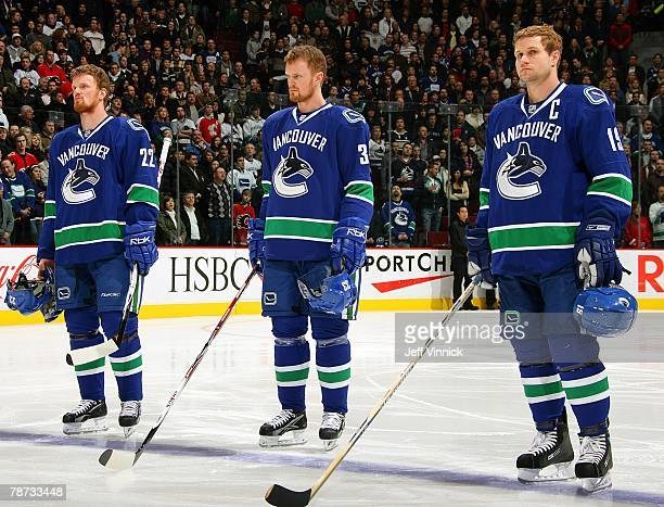 Daniel Sedin Henrik Sedin and Markus Naslund of the Vancouver Canucks listen to the national anthems during their game against the Calgary Flames at...