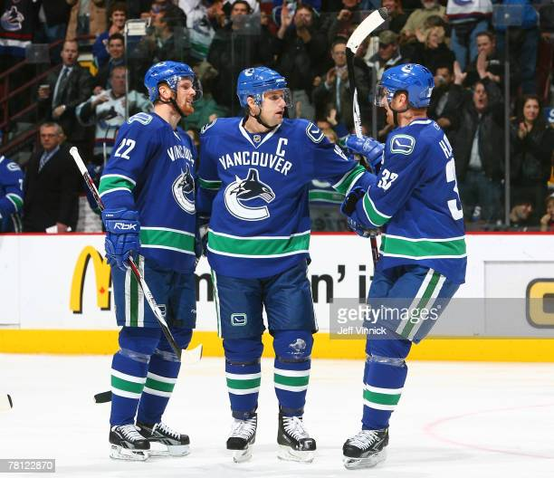 Daniel Sedin Markus Naslund and Henrik Sedin of the Vancouver Canucks celebrate a goal against the Anaheim Ducks during their game at General Motors...