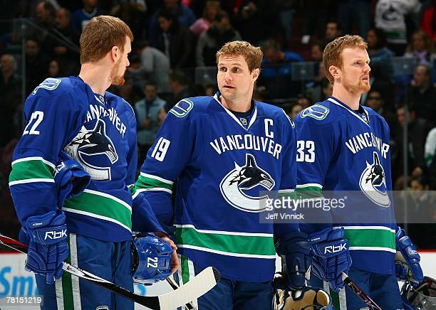 Daniel Sedin Markus Naslund and Henrik Sedin of the Vancouver Canucks listen to the national anthems before their game against the Anaheim Ducks at...