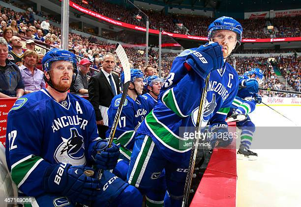 Daniel Sedin of and Henrik Sedin of the Vancouver Canucks look on from the bench during their NHL game against the Edmonton Oilers at Rogers Arena...
