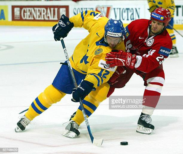 Daniel Sedin of Sweden fights for the puck with Frederik Akesson of Denmark in the Group C match between Sweden and Denmark the IIHF Men's World...