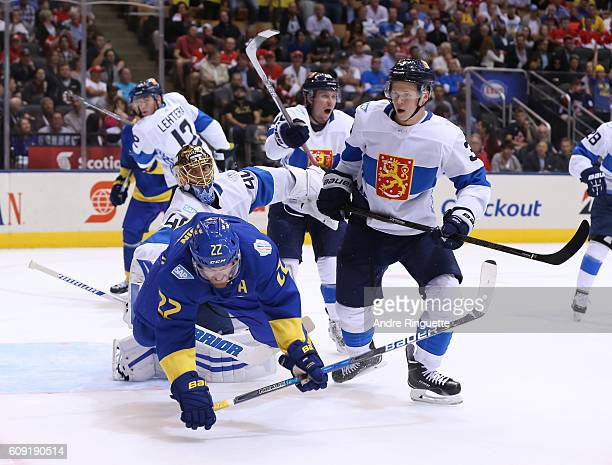 Daniel Sedin of Team Sweden gets knocked to the ice in front of Tuukka Rask and Olli Maatta of Team Finland during the World Cup of Hockey 2016 at...