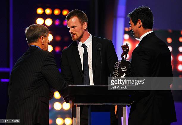 Daniel Sedin of the Vancouver Canucks accepts the Ted Lindsay Award from presenters Ted Lindsay and Mathieu Schneider during the 2011 NHL Awards at...
