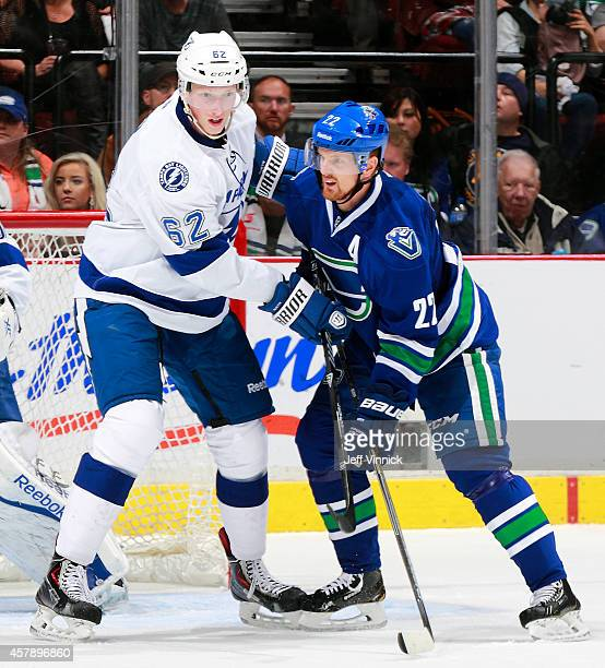 Daniel Sedin of the Vancouver Canucks and Andrej Sustr of the Tampa Bay Lightning during their NHL game at Rogers Arena October 18, 2014 in...