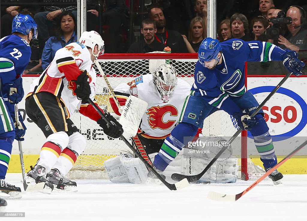 Daniel Sedin #22 of the Vancouver Canucks and Chris Butler #44 of the Calgary Flames watch as Karri Ramo #31 of the Flames makes a save on Ryan Kesler #17 of the Canucks during their NHL game at Rogers Arena April 13, 2014 in Vancouver, British Columbia, Canada.