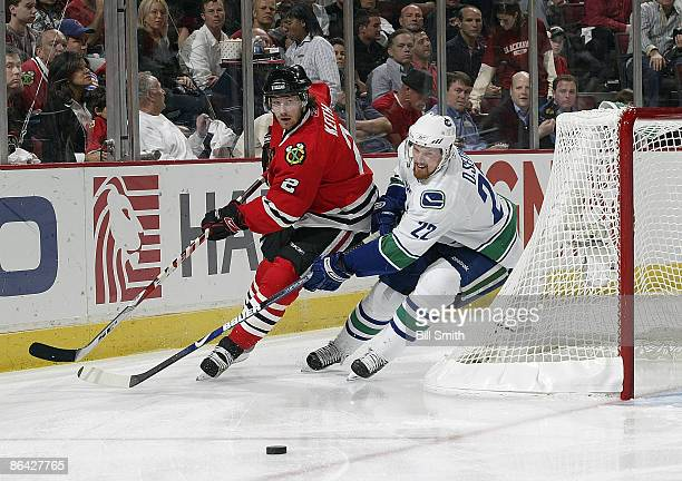 Daniel Sedin of the Vancouver Canucks and Duncan Keith of the Chicago Blackhawks chase the puck around the boards during game three of the Western...