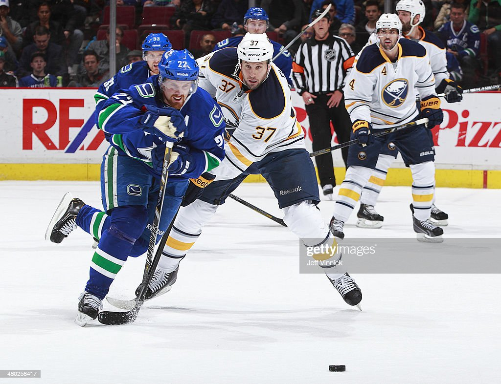 Daniel Sedin #22 of the Vancouver Canucks and Matt Ellis #37 of the Buffalo Sabres battle for the puck during their NHL game at Rogers Arena March 23, 2014 in Vancouver, British Columbia, Canada.