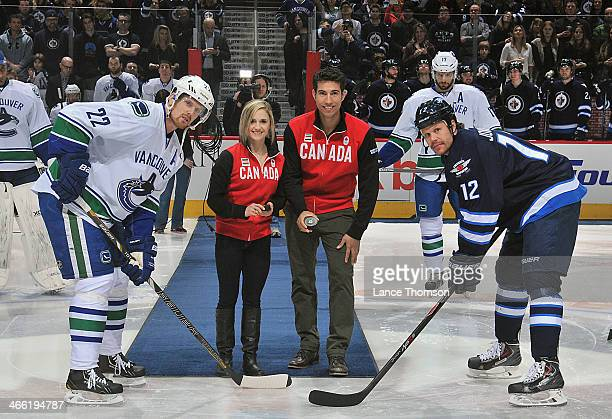 Daniel Sedin of the Vancouver Canucks and Olli Jokinen of the Winnipeg Jets pose with Canadian Olympic pairs figure skaters Paige Lawrence and Rudi...