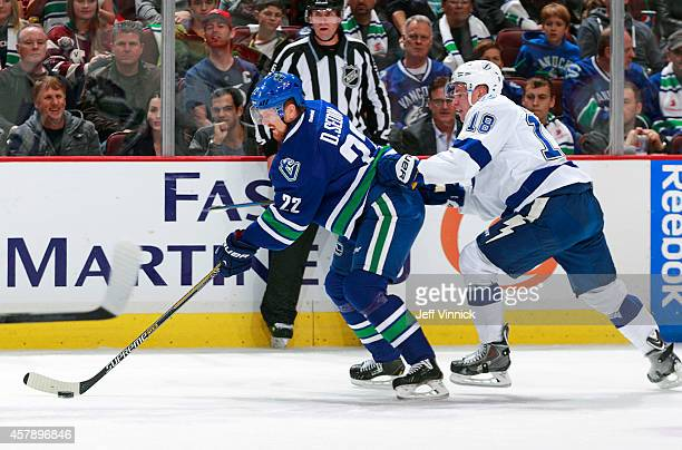 Daniel Sedin of the Vancouver Canucks and Ondrej Palat of the Tampa Bay Lightning skate up ice during their NHL game at Rogers Arena October 18, 2014...