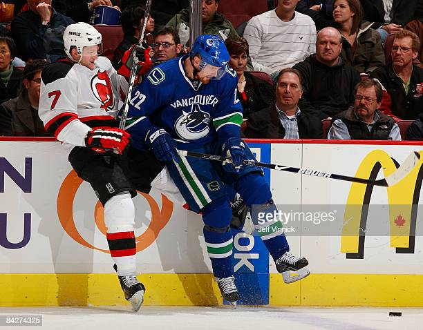 Daniel Sedin of the Vancouver Canucks and Paul Martin of the New Jersey Devils battle for the puck during their game at General Motors Place on...
