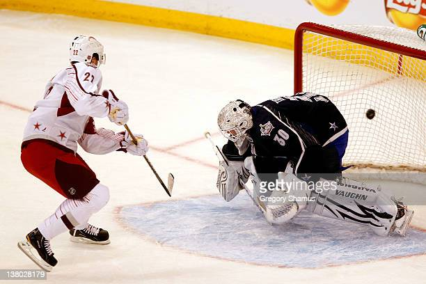 Daniel Sedin of the Vancouver Canucks and Team Alfredsson scores a goal in the third period against Tim Thomas of the Boston Bruins and Team Chara...