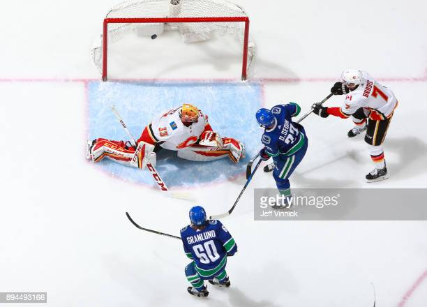 Daniel Sedin of the Vancouver Canucks and TJ Brodie of the Calgary Flames look on as Markus Granlund of the Vancouver Canucks scores on David Rittich...