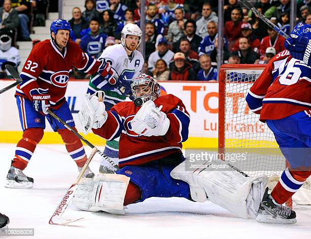Daniel Sedin of the Vancouver Canucks and Travis Moen of the Montreal Canadiens looks on as Carey Price of the Montreal Canadiens makes a save late...