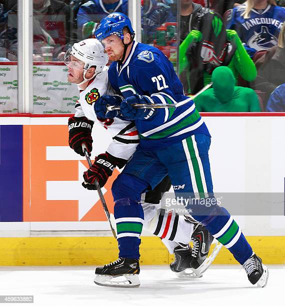 Daniel Sedin of the Vancouver Canucks checks Jonathan Toews of the Chicago Blackhawks during their NHL game at Rogers Arena November 23, 2014 in...