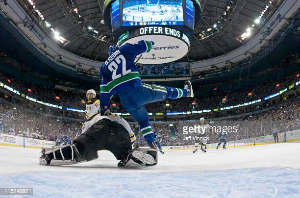 Daniel Sedin of the Vancouver Canucks collides with Tim Thomas of the Boston Bruins in Game Two of the 2011 NHL Stanley Cup Finals at Rogers Arena on...