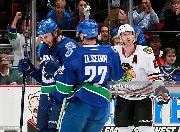 Daniel Sedin of the Vancouver Canucks congratulates goal scorer Zack Kassian while Duncan Keith of the Chicago Blackhawks looks up during their NHL...