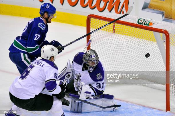 Daniel Sedin of the Vancouver Canucks fires the puck past goalie Jonathan Quick of the Los Angeles Kings as Sean O'Donnell of the Kings tries to help...