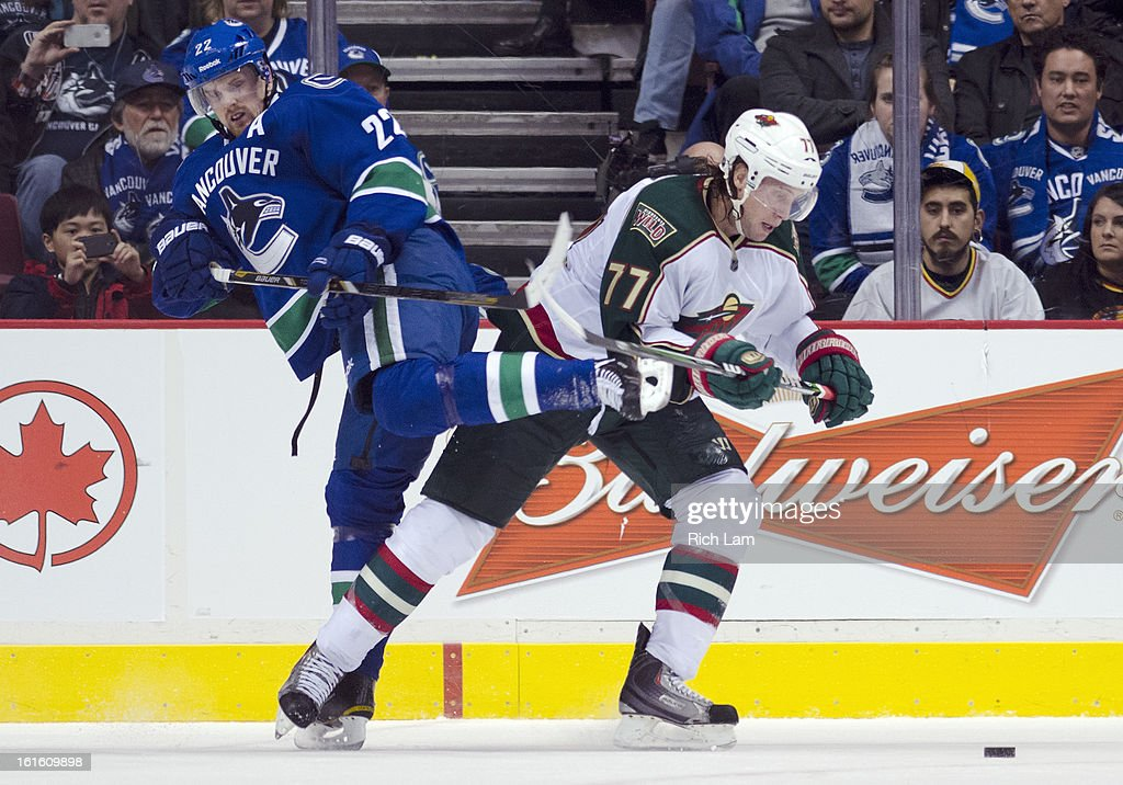Daniel Sedin #22 of the Vancouver Canucks gets tangled up with Tom Gilbert #77 of the Minnesota Wild while on the forecheck during the third period in NHL action on February 12, 2013 at Rogers Arena in Vancouver, British Columbia, Canada.