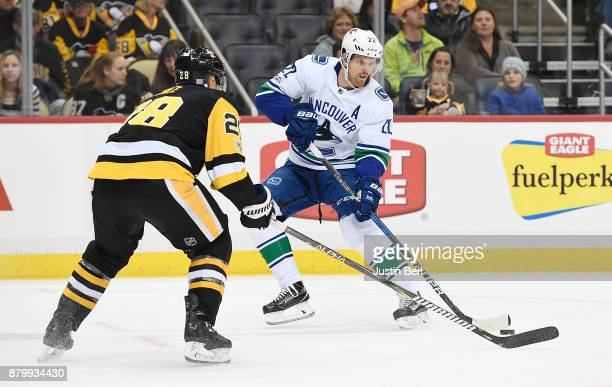 Daniel Sedin of the Vancouver Canucks handles the puck as Ian Cole of the Pittsburgh Penguins defends in the first period during the game at PPG...
