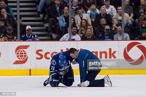 Daniel Sedin of the Vancouver Canucks is assisted by the team athletic therapist on the ice against the Pittsburgh Penguins on January 7 2014 at...