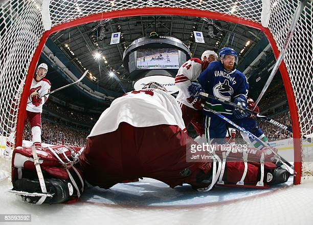 Daniel Sedin of the Vancouver Canucks is checked off the puck by Kurt Sauer of the Phoenix Coyotes as Ilya Bryzgalov of the Coyotes makes a save...