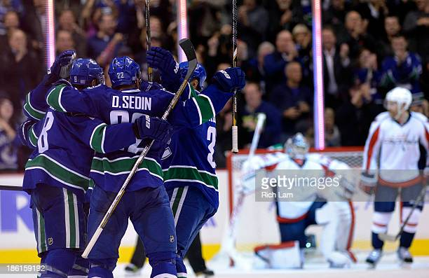 Daniel Sedin of the Vancouver Canucks is congratulated by Henrik Sedin and Chris Tanev after scoring a goal on goalie Michal Neuvirth of the...
