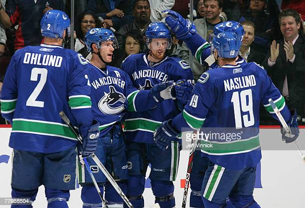 Daniel Sedin of the Vancouver Canucks is congratulated by teammates Mattias Ohlund Brendan Morrison and Markus Naslund after scoring against the...