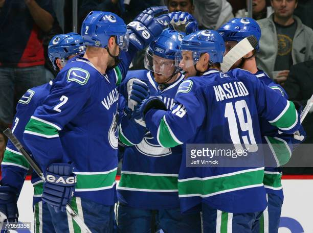 Daniel Sedin of the Vancouver Canucks is congratulated by teammates Mattias Ohlund Brendan Morrison Henrik Sedin and Markus Naslund after scoring...