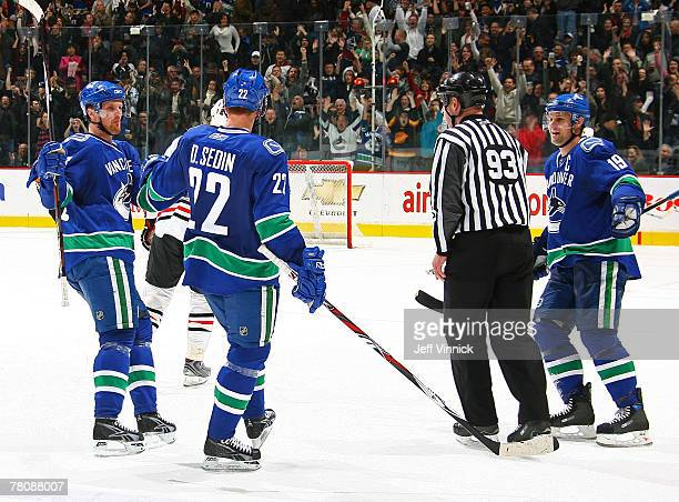 Daniel Sedin of the Vancouver Canucks is congratulated by teammates Henrik Sedin and Markus Naslund after scoring against the Chicago Blackhawks...