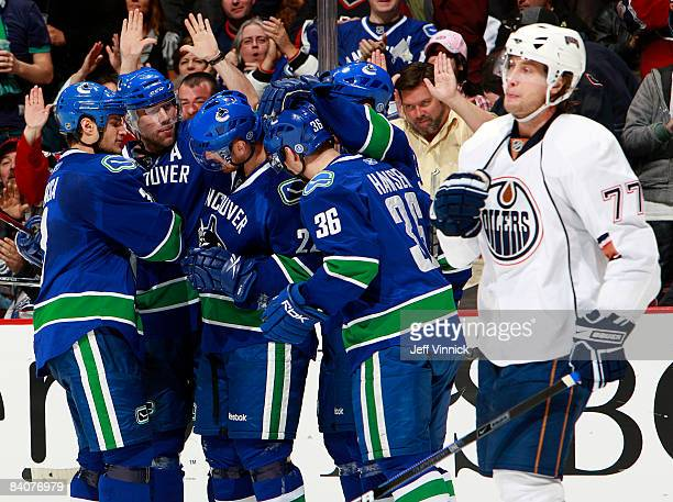 Daniel Sedin of the Vancouver Canucks is congratulated by teammates after scoring his second goal of the game while Tom Gilbert of the Edmonton...