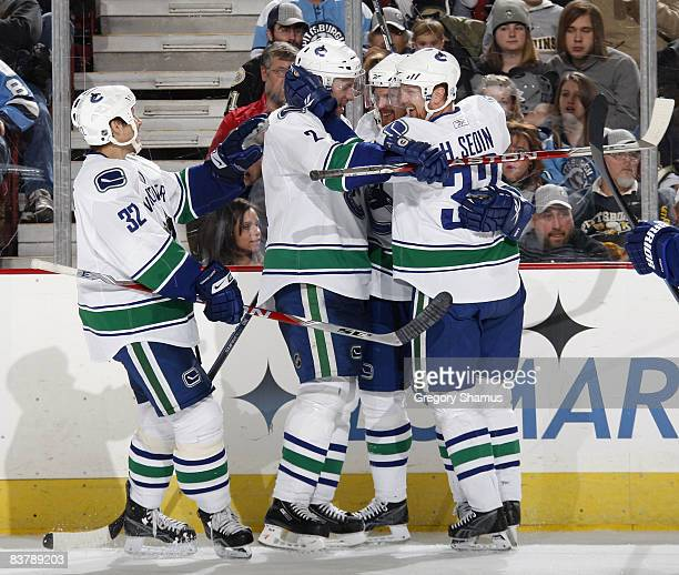 Daniel Sedin of the Vancouver Canucks is congratulated on his second period goal by Henrik Sedin Mattias Ohlund and Lawrence Nycholat while playing...