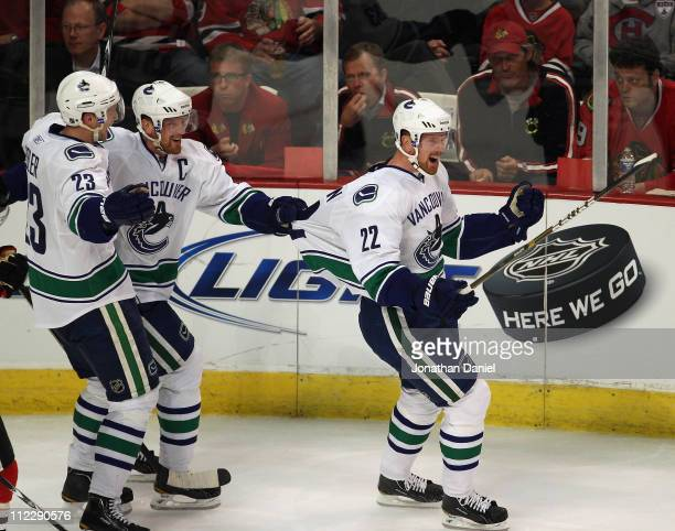 Daniel Sedin of the Vancouver Canucks is grabbed by the jersey by his brother Henrik Sedin after scoring a goal in the 2nd period against the Chicago...