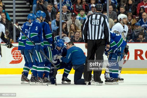 Daniel Sedin of the Vancouver Canucks is tended to by the team therapist after taking a puck to the torso against the Pittsburgh Penguins on January...
