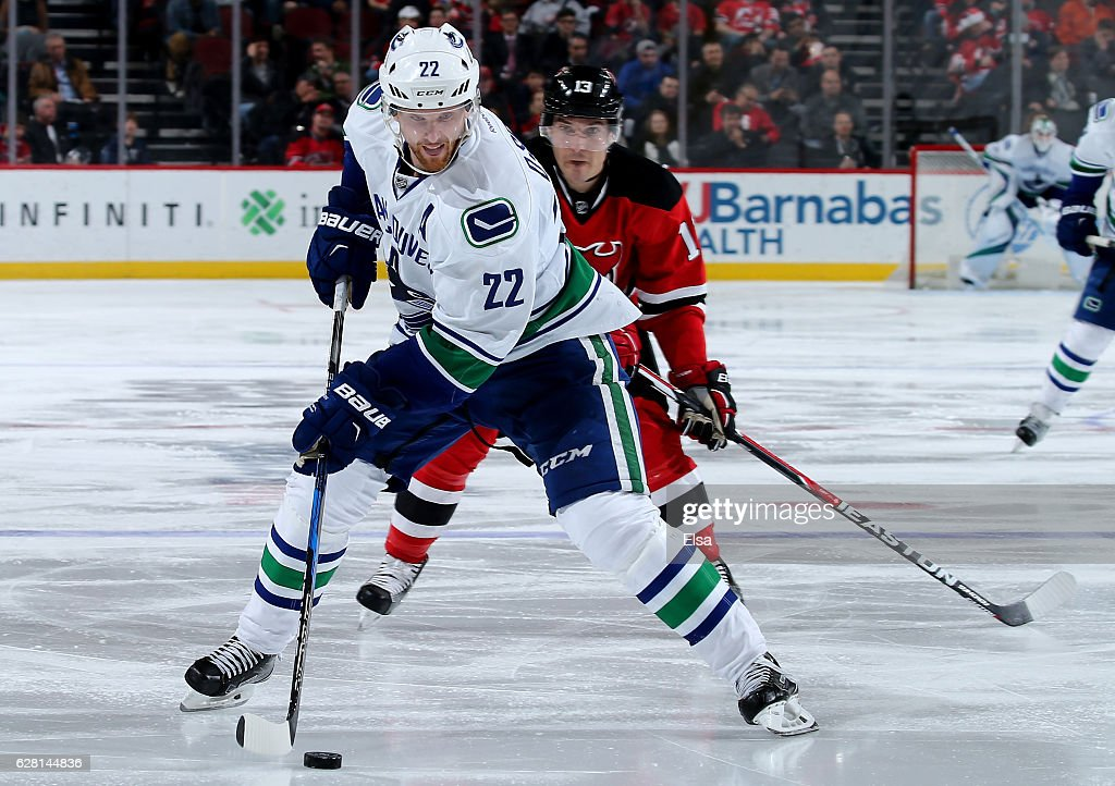 Daniel Sedin #22 of the Vancouver Canucks passes the puck as Michael Cammalleri #13 of the New Jersey Devils defends on December 6, 2016 at Prudential Center in Newark, New Jersey.