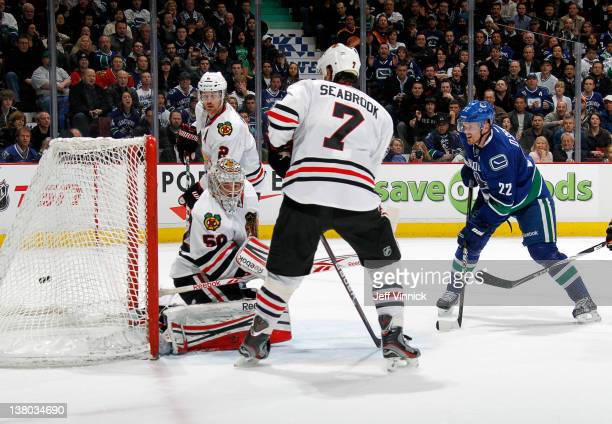 Daniel Sedin of the Vancouver Canucks scores in overtime against defenders Brent Seabrook Duncan Keith and Corey Crawford of the Chicago Blackhawks...