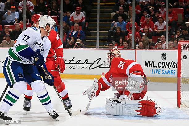 Daniel Sedin of the Vancouver Canucks scores on Jimmy Howard of the Detroit Red Wings during a NHL game at Joe Louis Arena on February 24 2013 in...