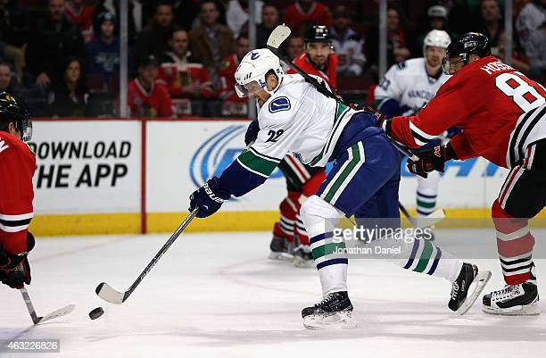 Daniel Sedin of the Vancouver Canucks shoots the gamewinning goal under pressure from Marian Hossa of the Chicago Blackhawks at the Chicago...