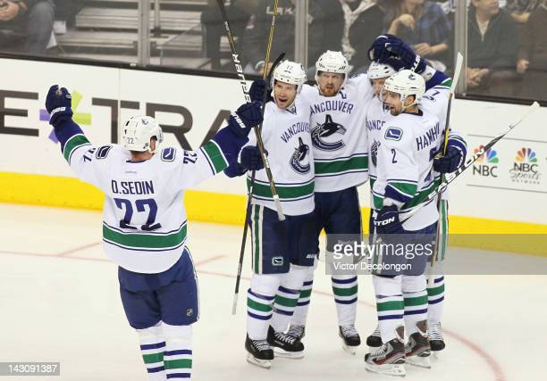Daniel Sedin of the Vancouver Canucks skates over to teammates Ryan Kesler Henrik Sedin Alexander Edler and Dan Hamhuis after a goal by Edler in the...