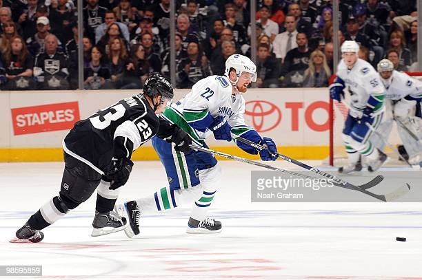 Daniel Sedin of the Vancouver Canucks skates with the puck against Dustin Brown of the Los Angeles Kings in Game Three of the Western Conference...