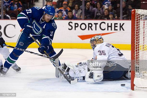 Daniel Sedin of the Vancouver Canucks slides a backhand shot past goalie Nikolai Khabibulin of the Edmonton Oilers for his second goal of the night...