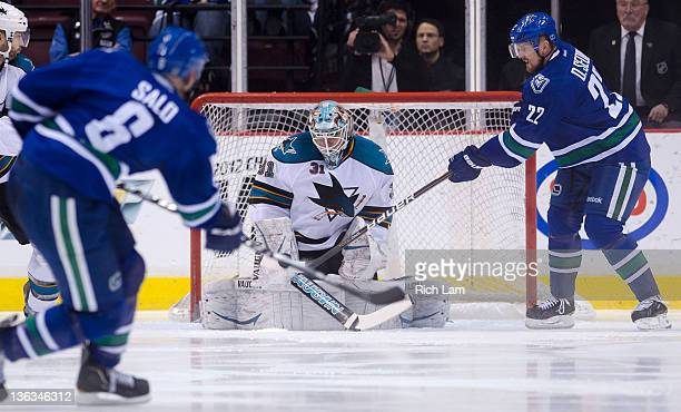 Daniel Sedin of the Vancouver Canucks tries to deflect the shot of teammate Sami Salo past goalie Antti Niemi of the San Jose Sharks during the...