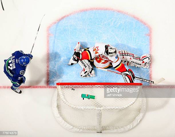 Daniel Sedin of the Vancouver Canucks watches as the shot of teammate Markus Naslund gets past Miikka Kiprusoff of the Calgary Flames for a Canuck...