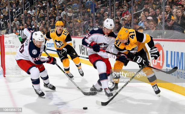 Daniel Sprong of the Pittsburgh Penguins and Markus Nutivaara of the Columbus Blue Jackets battle for the puck at PPG Paints Arena on November 24...