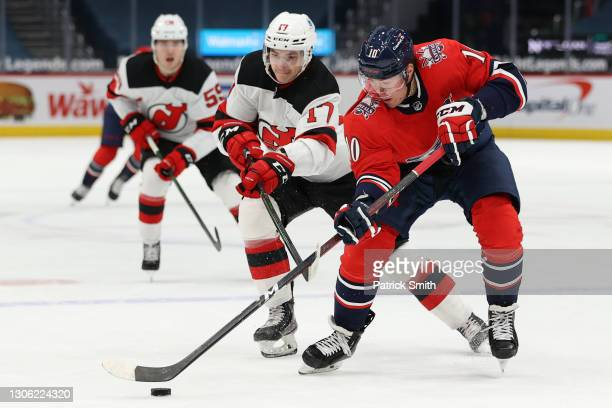 Daniel Sprong of the Washington Capitals skates past Yegor Sharangovich of the New Jersey Devils during the second period at Capital One Arena on...